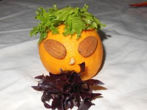 Orange mit Augen, Nase, Mund und Haaren